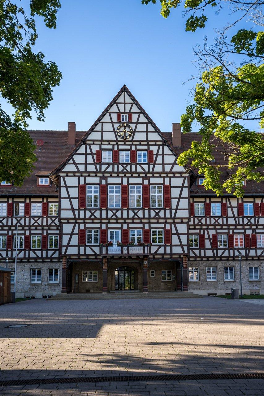 Ein großes historisches Fachwerkgebäude mit vielen Fenstern, roten Fensterläden und einer großen Uhr. Davor ist ein großer Platz.