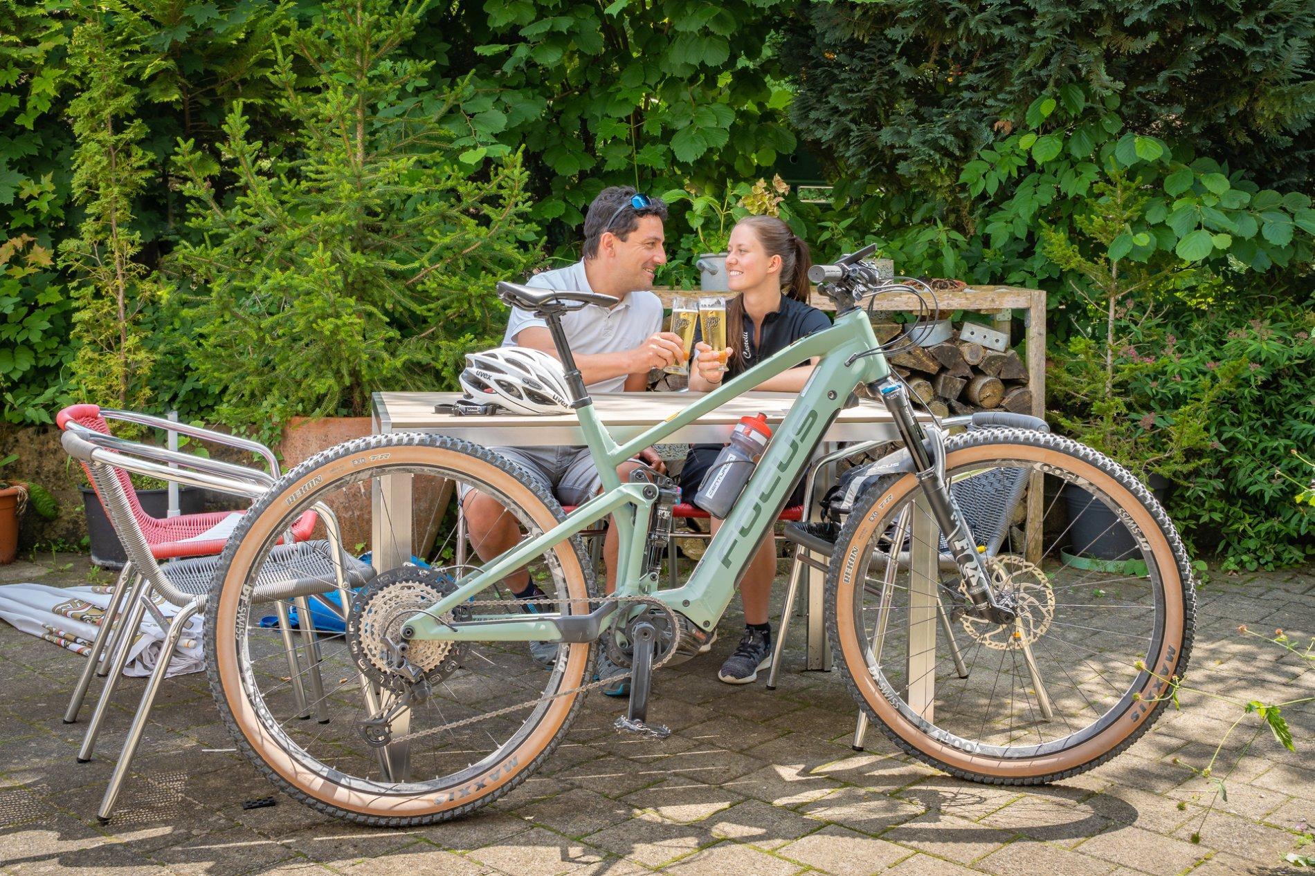 Drei Radfahrer*innen fahren auf einem Schotterweg in die Richtung eines Schilds, an dem mehrere Radwegweiser in alle möglichen Richtungen hängen. Es ist sonnig und warm.