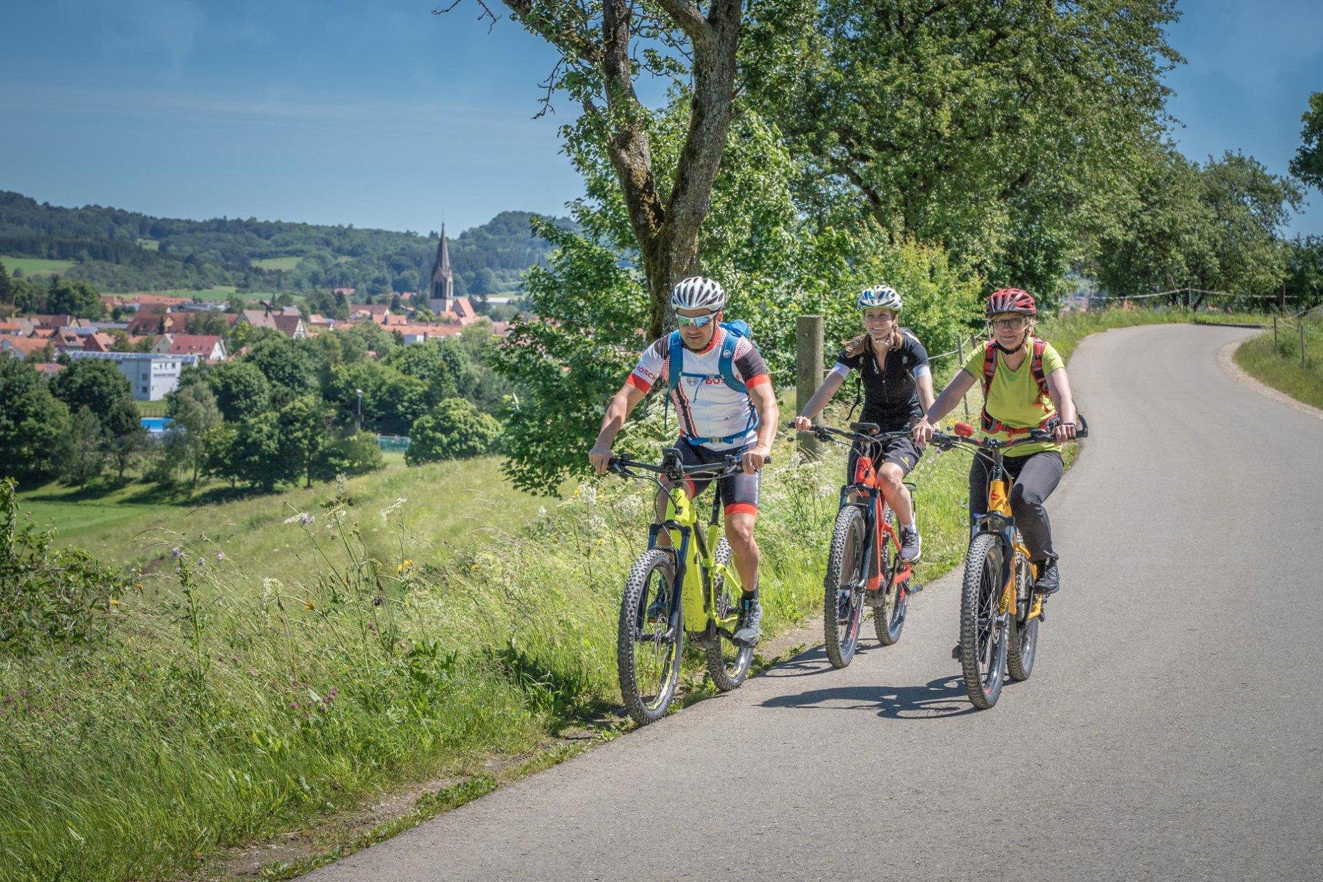 Drei Radfahrer*innen fahren mit E-Bikes auf einem Teerweg und lächeln. Am Rand ist eine Sommerwiese und einige Bäume. Im Hintergrund ist eine Stadt mit einer Kirche zu sehen.