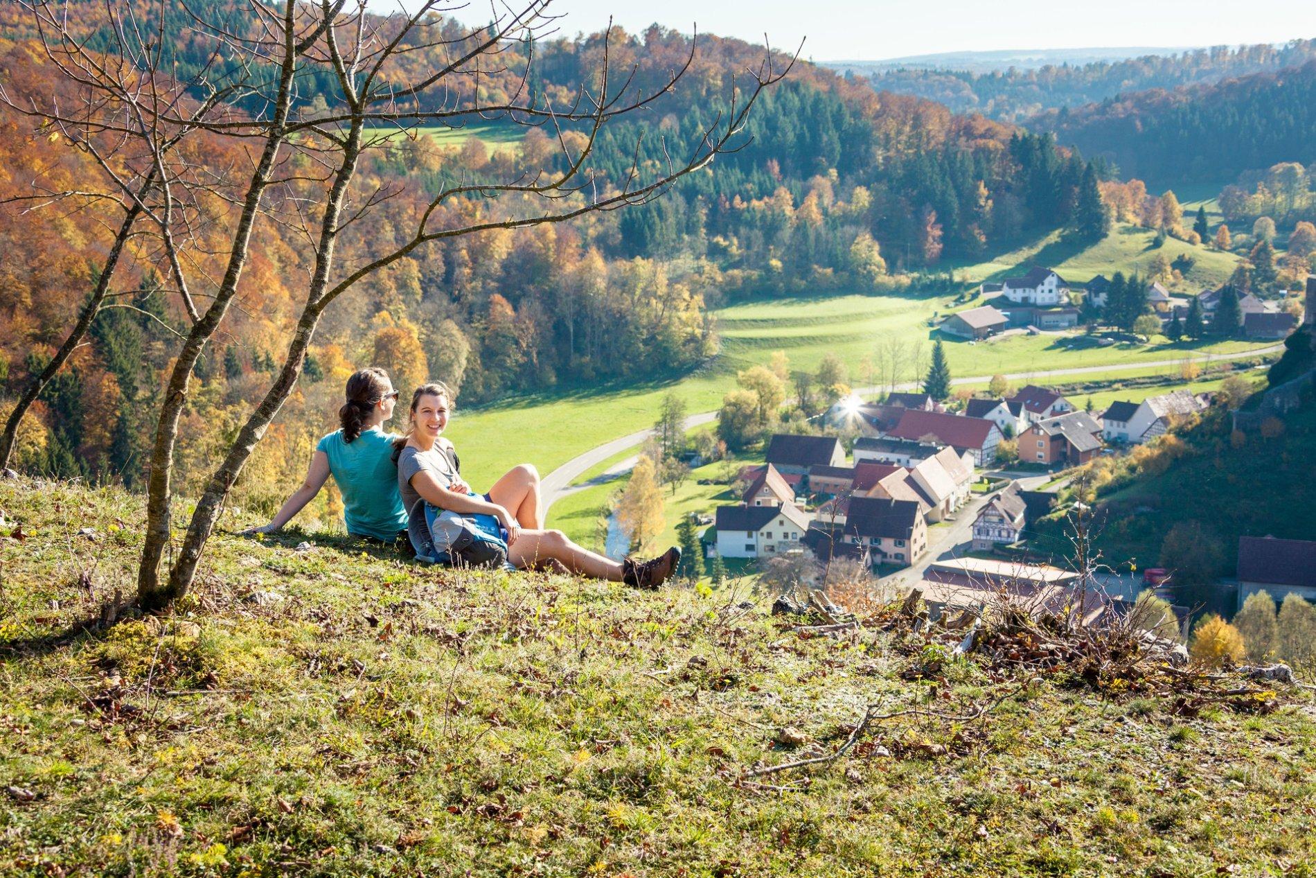 Zwei Wanderer*innen sitzen auf einem Hügel und lehnen sich aneinander an. Vor ihnen ist ein Ausblick über ein kleines Dorf im Tal, durch das ein Fluss fließt. Ringsherum ist Wald in Herbstfarben. Die Sonne scheint.