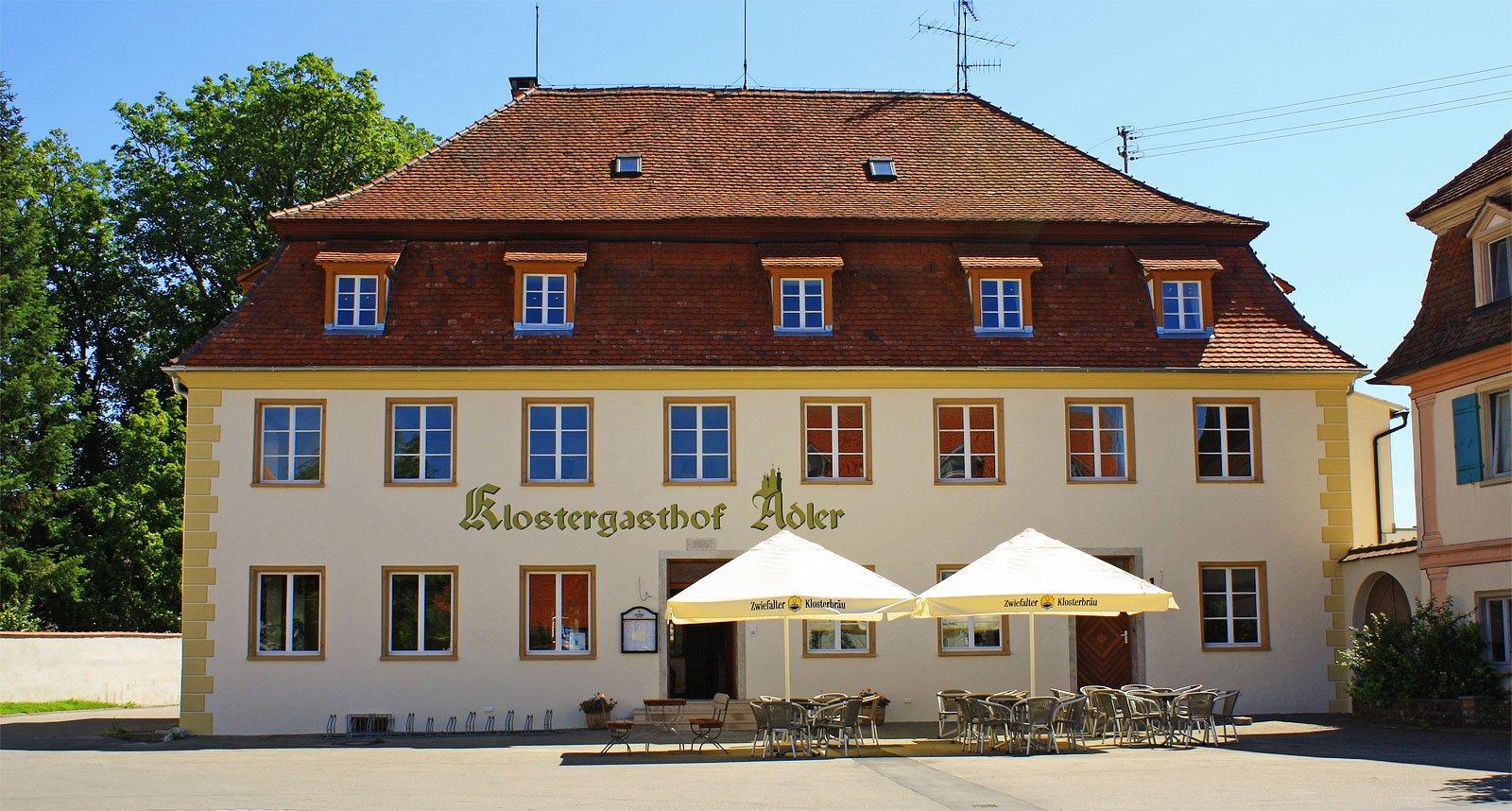 Ein historisches Haus mit der Aufschrift Klostergasthof Adler. Davor zwei Sonnenschirme und mehrere Tische und Stühle.