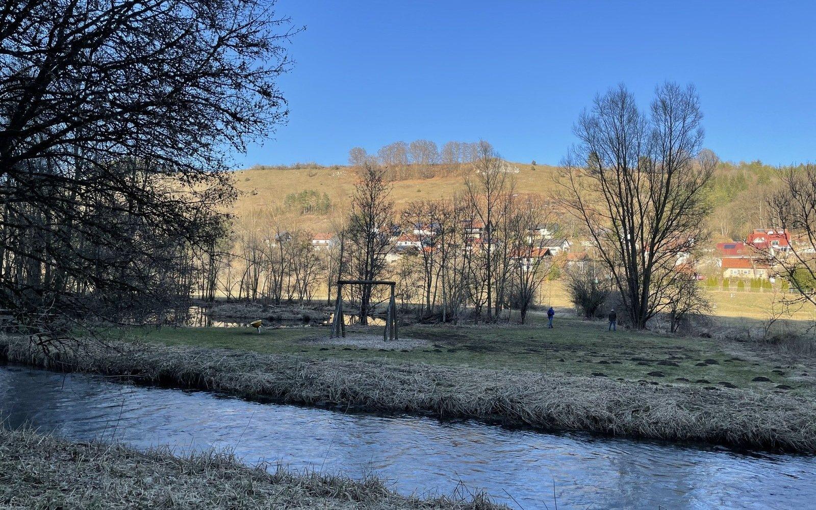 im Vordergrund ein Fluß, dahinter ein Spielplatz mit Kletterspinne im Hintergrund eine Häusersiedlung