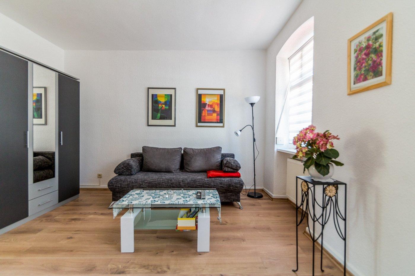 Helles Wohnzimmer mit grauer Couch und Schrank