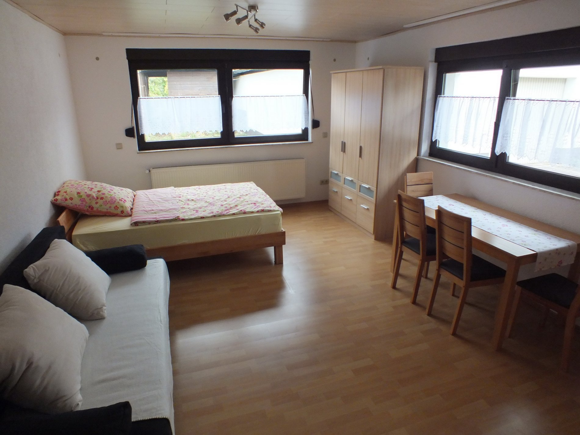 Schlafzimmer mit Einzelbett, Couch, Kleiderschrank und einem Tisch mit drei Stühlen