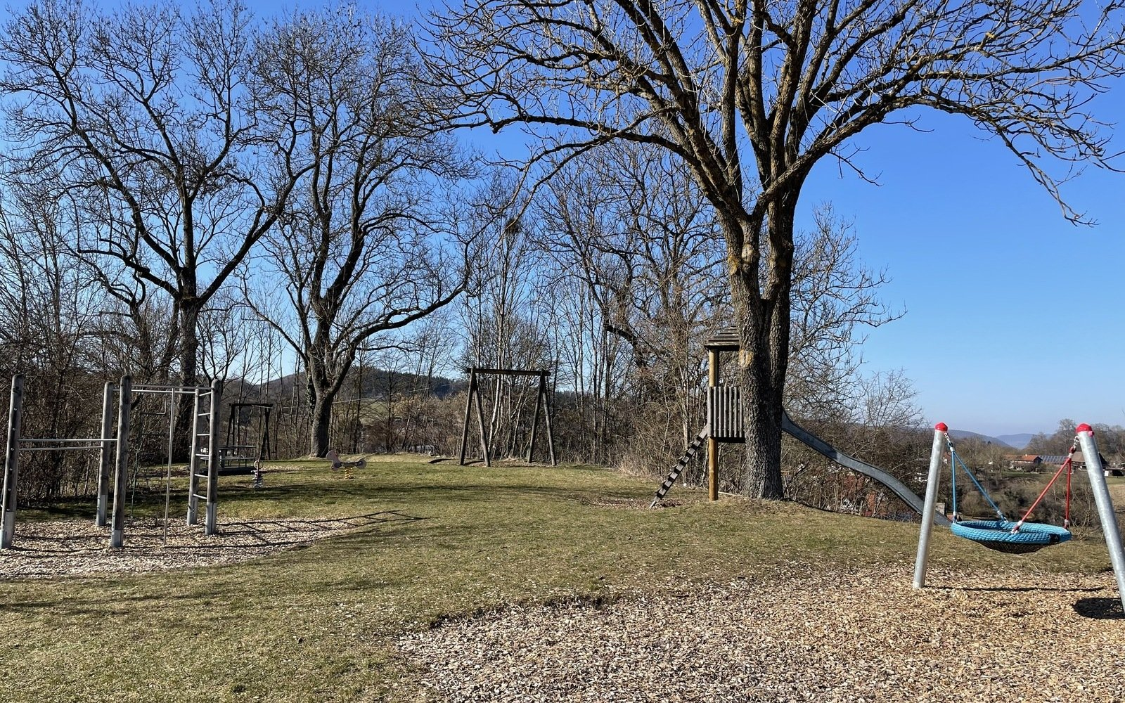 Ein Spielplatz mit einem Klettergerüst, einer Vogelnestschaukel und einer Rutsche bei strahlend blauem Himmel