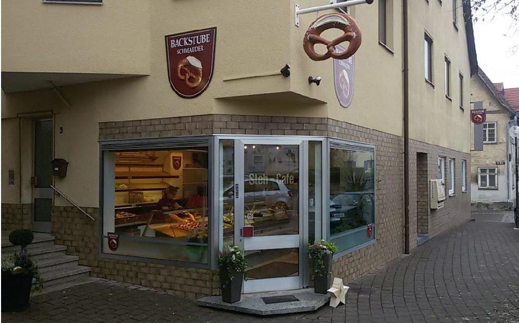 Bäckerei Schmauder von außen, über dem Schaufenster rechts hängt eine große Brezel. Über dem Schaufenster links hängt ein Schild mit einer Brezel daruf und der Aufschrift Backstube Schmauder