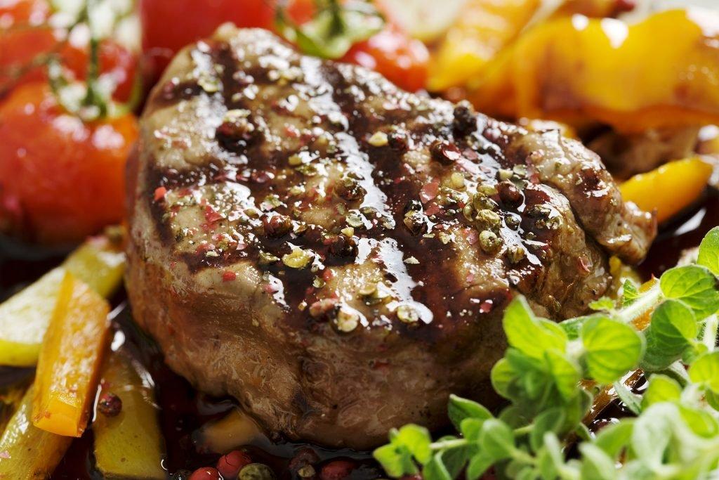 Ein Steak mit viel Gewürzen ganiert auf Salat, Pommes und Gemüse.
