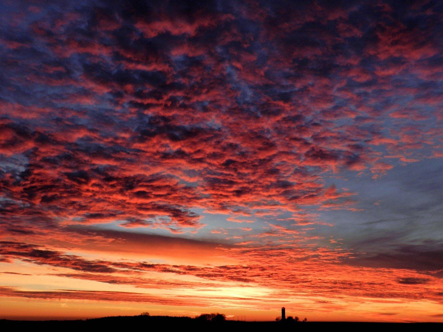 Ein Sonnenuntergang mit einigen Wolken am rot-orange-gelb-blau leuchtenden Himmel. Am Horizont ist die Silhoutte eines Turms und mehreren Bäumen.