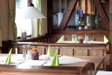 Ein Raum mit mehreren gedecketen Tischen und Sitzbänken aus Holz.