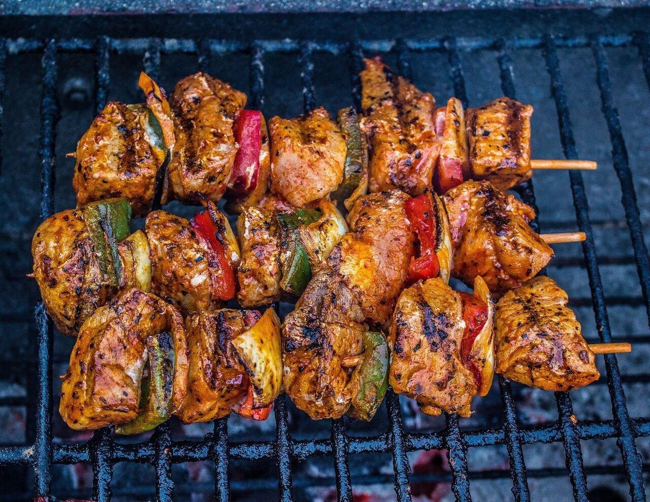 Auf einem Grill liegen drei Spiese mit Fleisch und Gemüse.