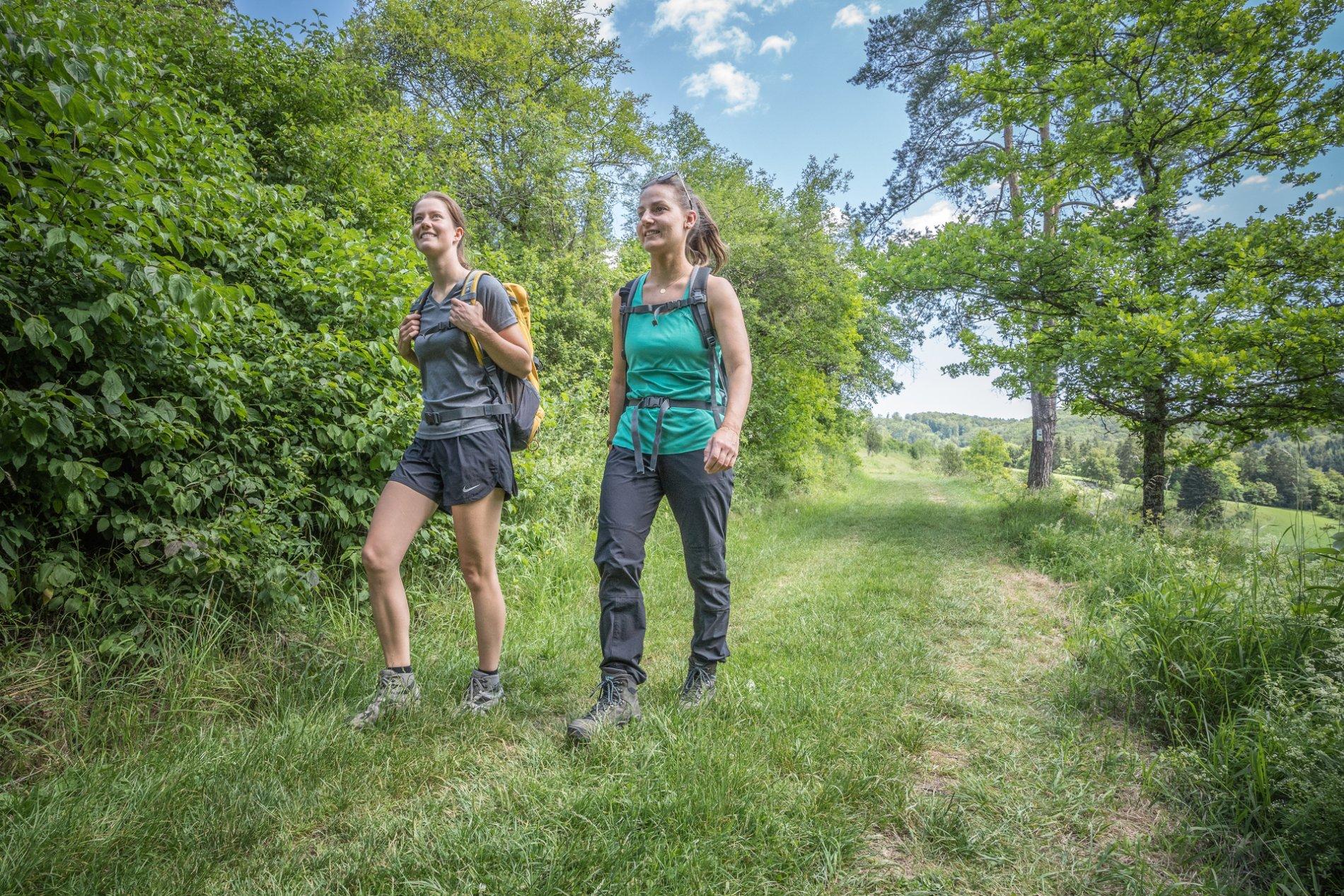 Zwei Wanderer*innen laufen über einen Wiesenweg und lächeln. Links und rechts sind Hecken und Bäume. Neben dem Weg wächst das Gras hoch. Es ist sonnig und warm.