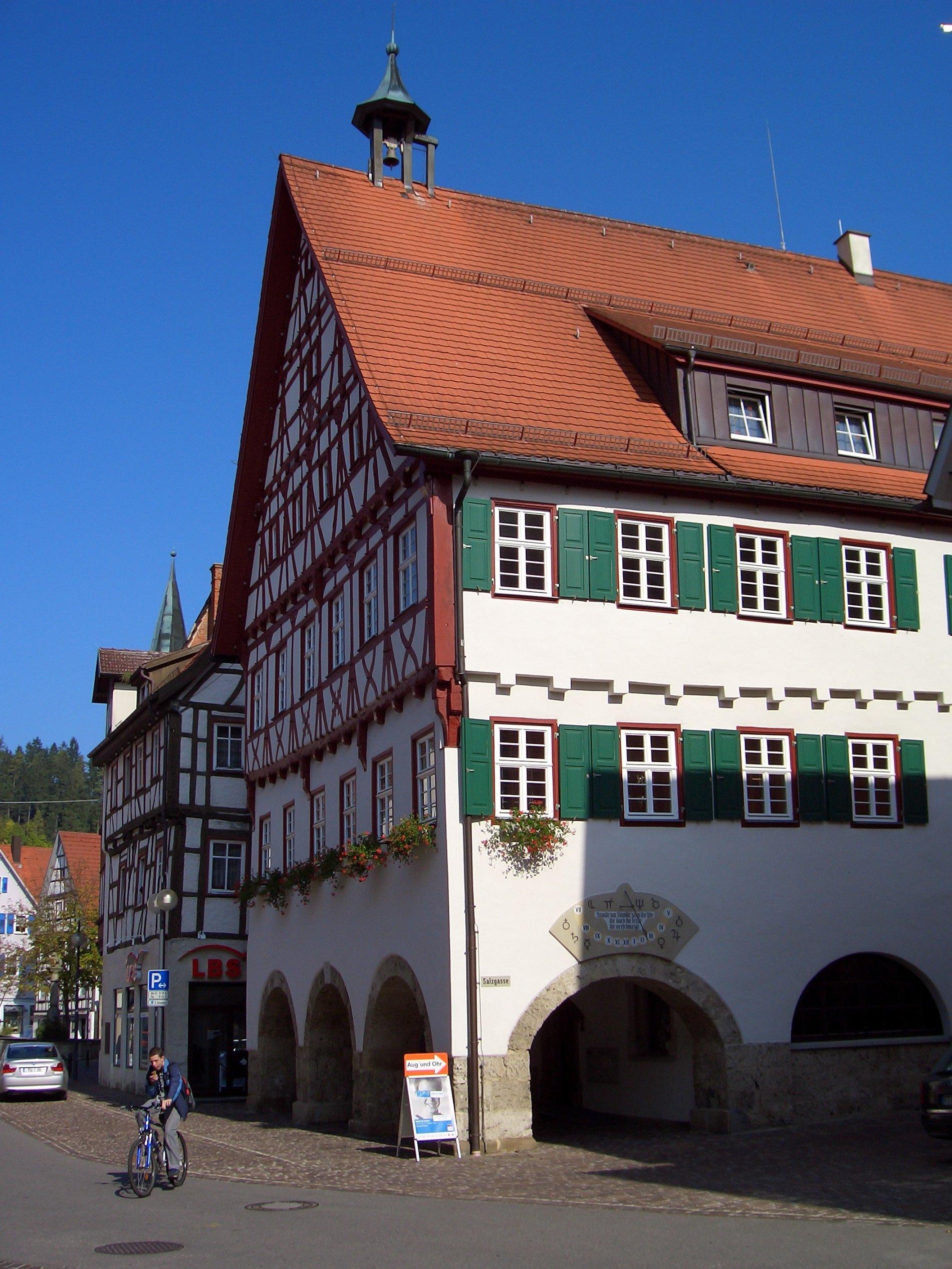An den Fenstern vom Rathaus sind Blumen und grüne Fensterläden angebracht. Vor dem Rathaus ist eine Person mit dem Fahrrad. Auf dem Dach ist ein kleiner Turm mit einer Glocke. Der Himmel ist blau.