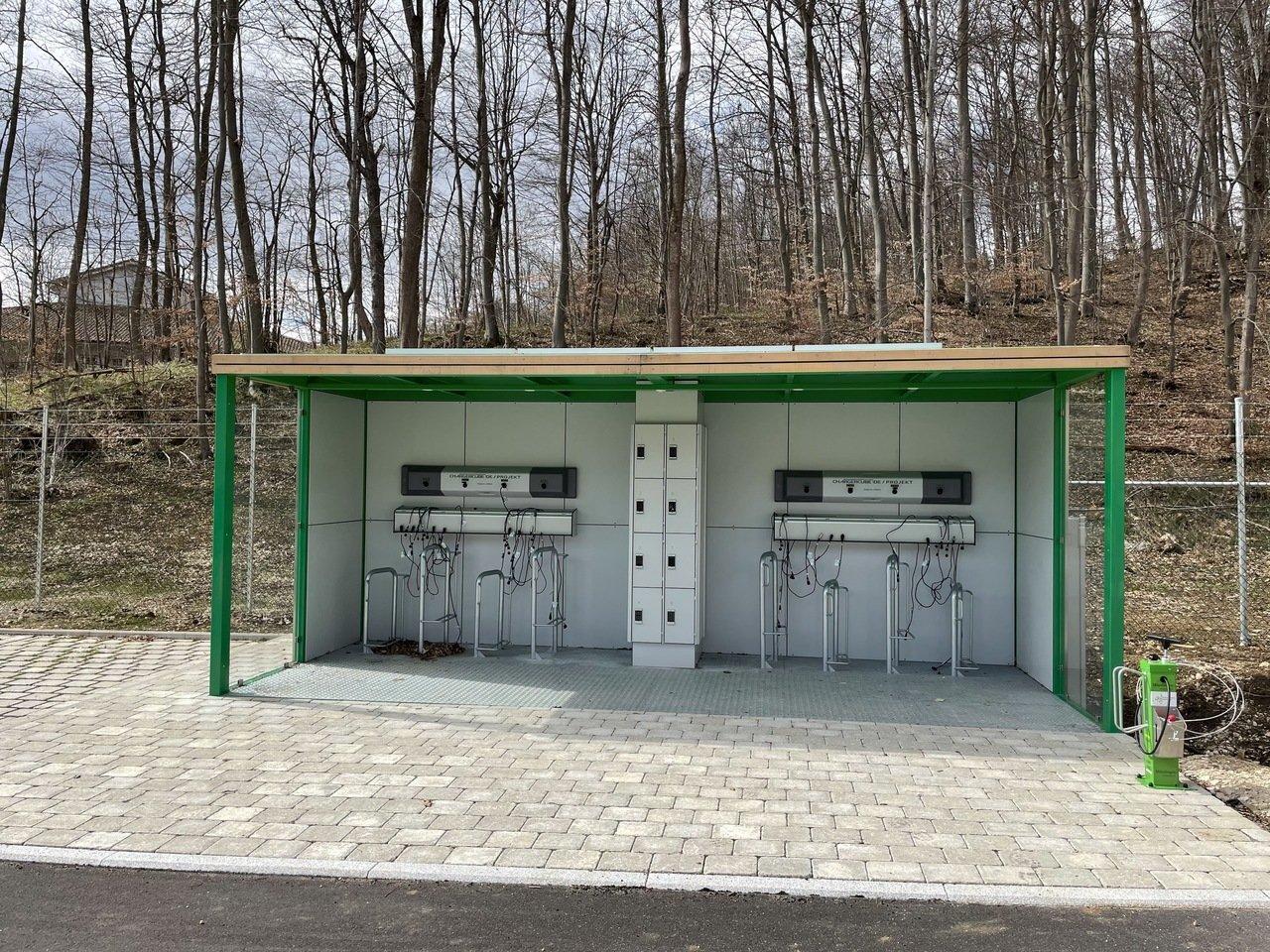 Im Vordergrund eine grüne E-Bike Ladestation mit vielen Anschlüssen. In der Mitte der Ladestation gibt es Schließfächer. Rechts daneben ist eine Radservice Station mit verschiedenen Werkzeugen.