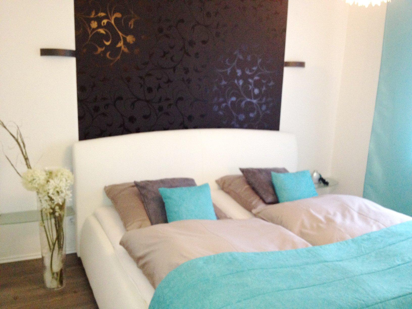Weißes Schlafzimmer mit türkisen Details