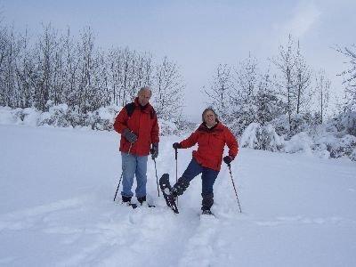 zwei Personen mit roten Jacken stehen mit Schneeschuhen im tief verschneiten Gelände