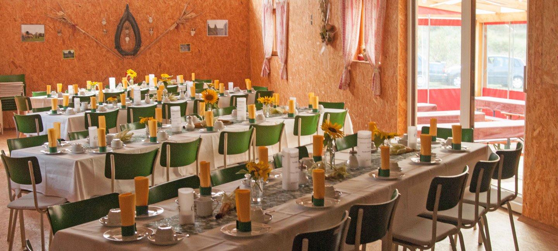 Ein Raum mit mehreren gedeckten langen Tafeln und mehreren Stühlen.
