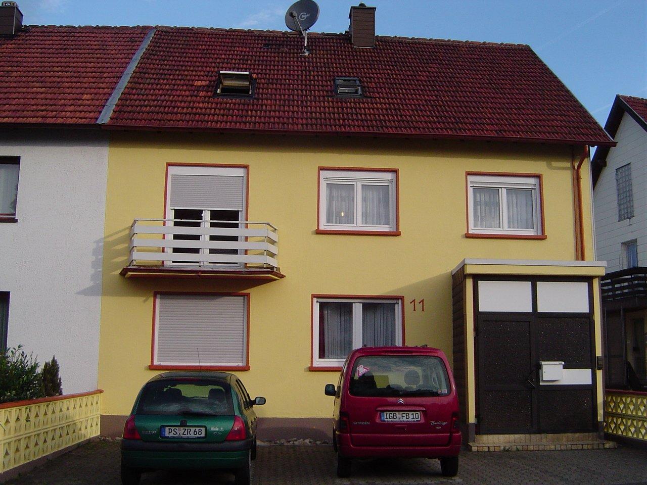 Das Haus Felix von vorne mit gelber Fasade und Stellplatz für das Auto