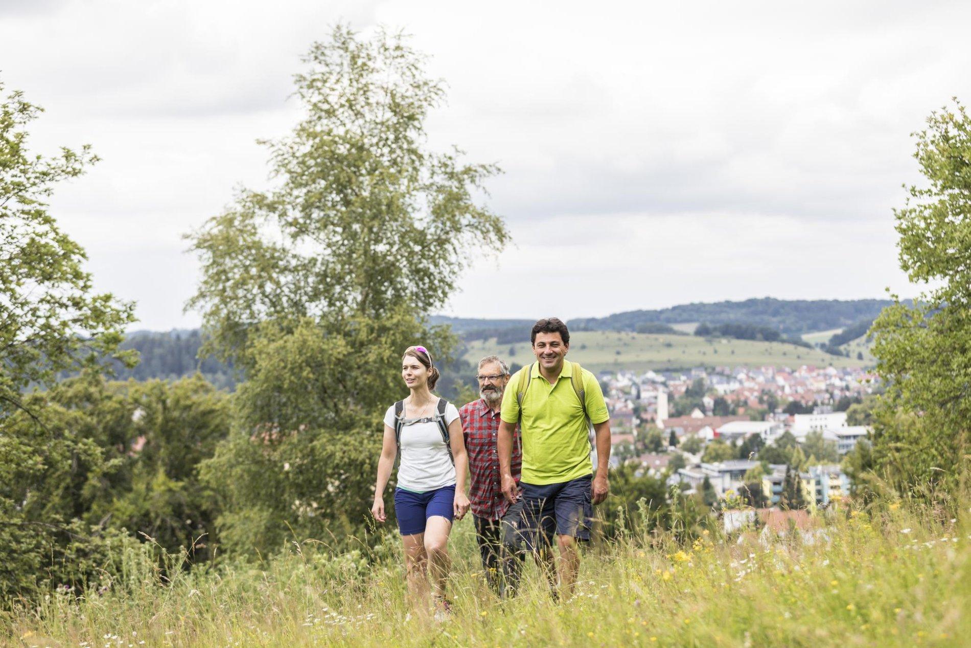 Drei Personen laufen durch das kniehohe Gras in dem dazwischen viele verschiedene Blumen blühen. Sie lächeln und tragen kurze sportliche Kleidung. Im Hintergrund ist verschwommen eine Stadt zu sehen.