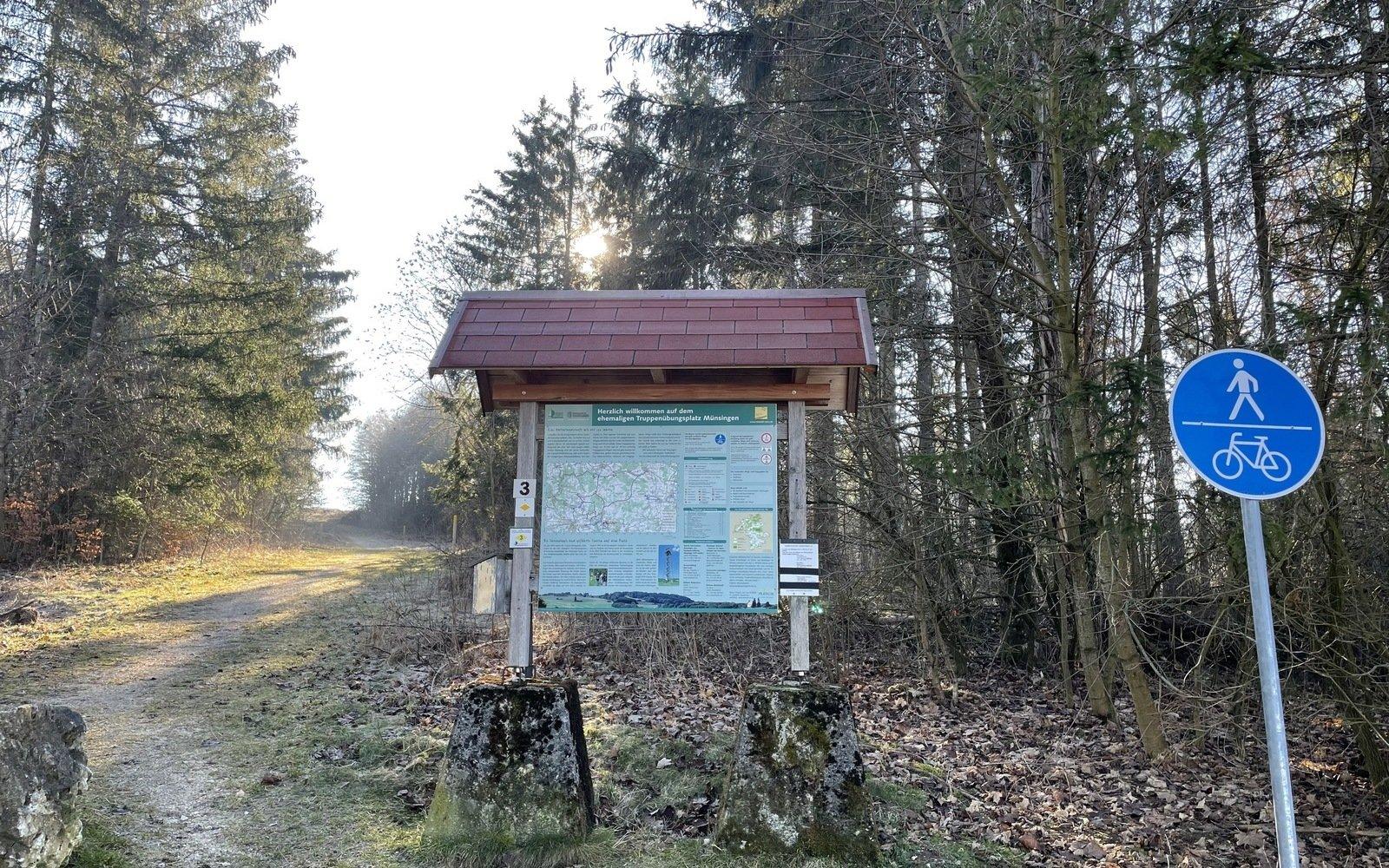 Eine grüne Wanderparkplatztafel auf zwei Betonsockeln, im Hintergrund ein Waldstück