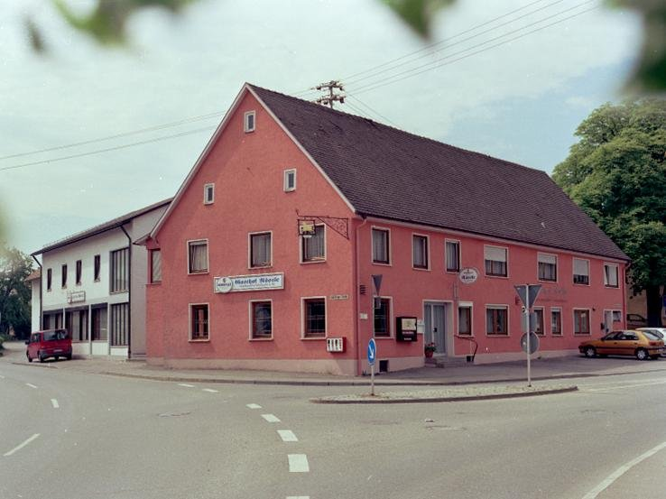 Ein rotes Haus an einer Straßenkreuzung.