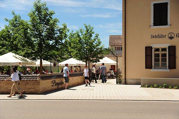 Vor einem Haus ist ein großer Biegarten mit mehreren Personen, Sonnenschirmen und ein paar Bäumen.