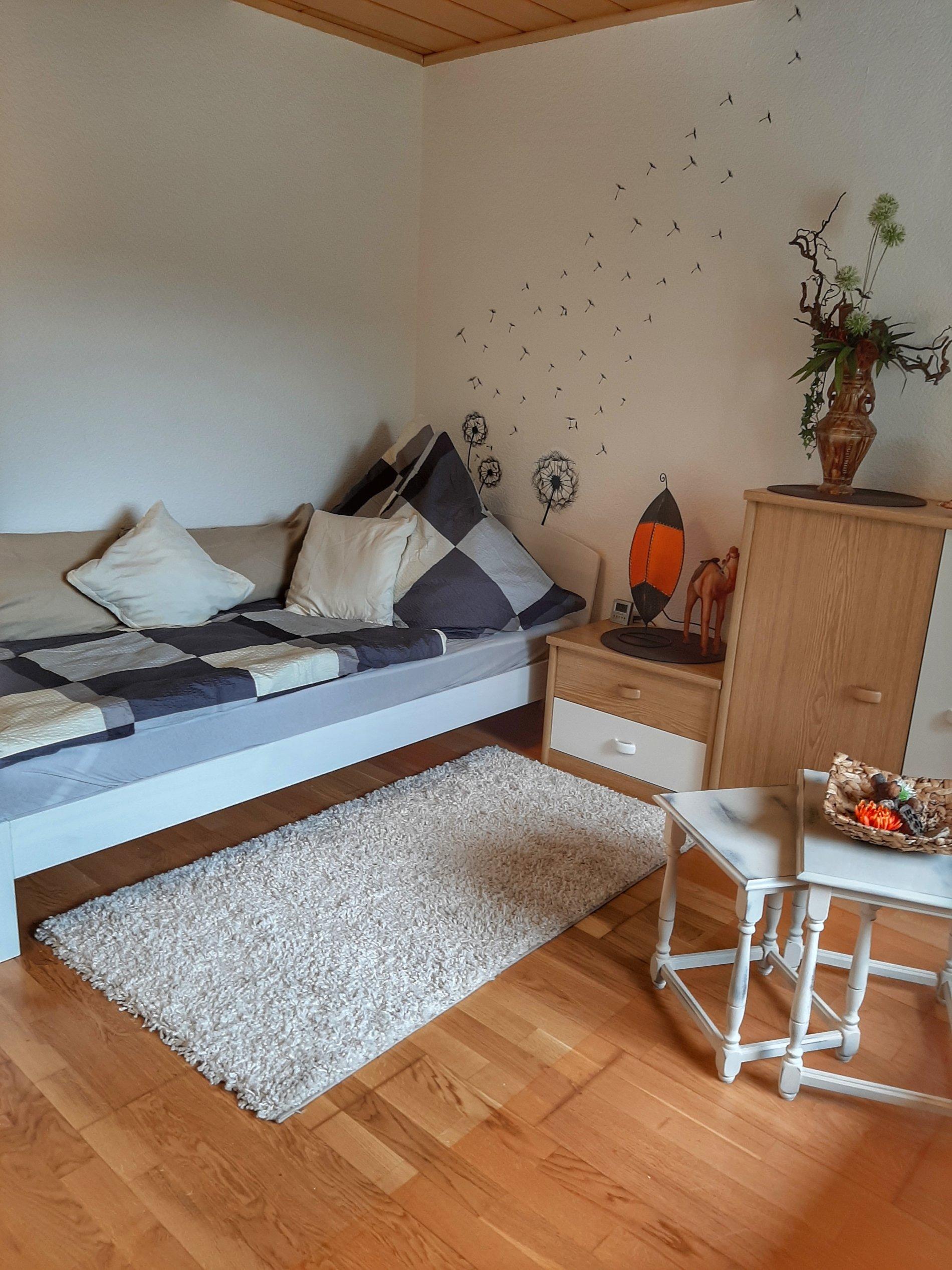 Einzelbett mit Nachttisch, Teppich und einem kleinen Tisch auf Pakett