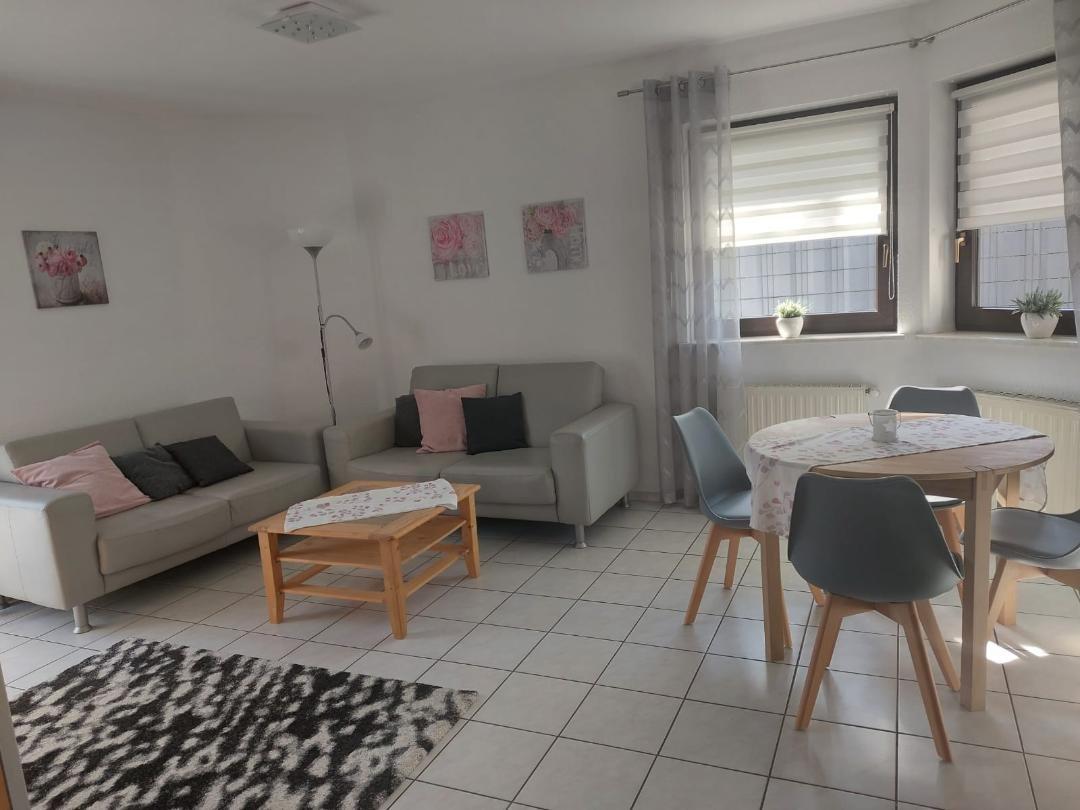 Runder Tisch mit vier Stühlen, zwei Sofas mit Couchtisch und zwei Fenster