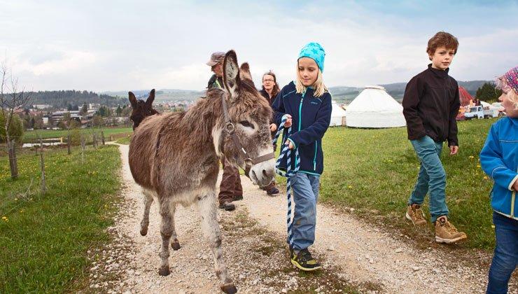 Ein Kind führt einen Esel an einem blau-schwarzen Strick und hat einen konzentrierten Blick. Drumherum spielen weitere Kinder. Im Hintergrund sind zwei Erwachsene und ein weiterer Esel.