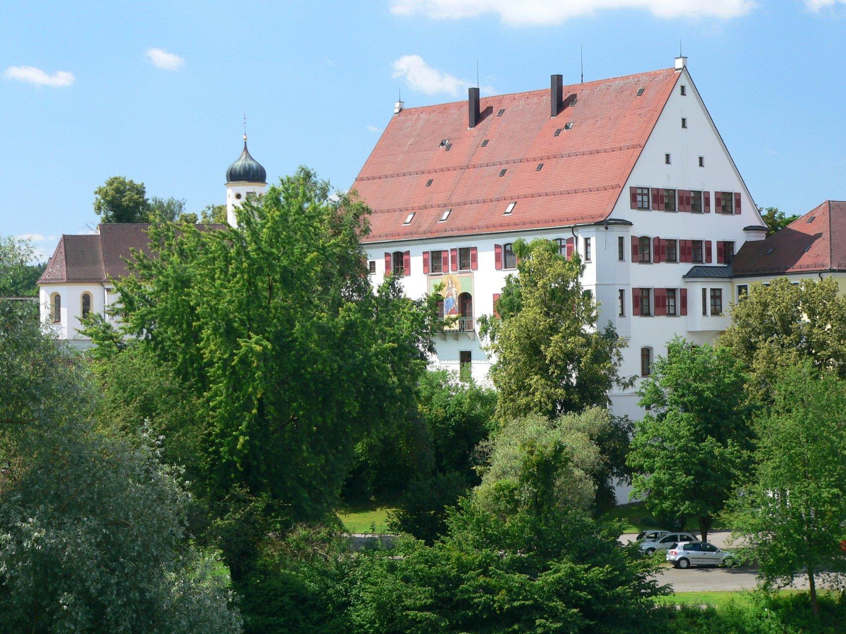 Ein großes Haus mit roten Fensterläden und einem gemalten Bild auf der Hausfassade an der Seite am Balkon. Daneben ist eine Kirche. Ringsherum sind einige Bäume.