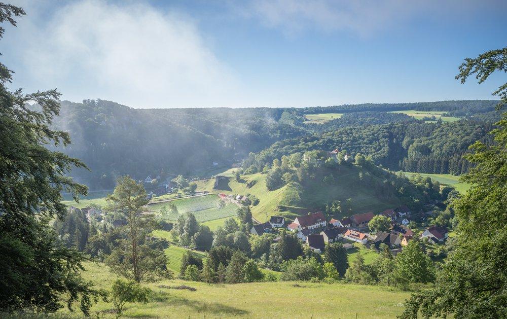 Ein Blick von einem Hügel auf eine Burg, die sich auf dem gegenüberligenden Hügel befindet, ein Dorf im Tal und viele Wiesen und Wälder. Die Sonne scheint und vereinzelt steht Nebel in der Luft.