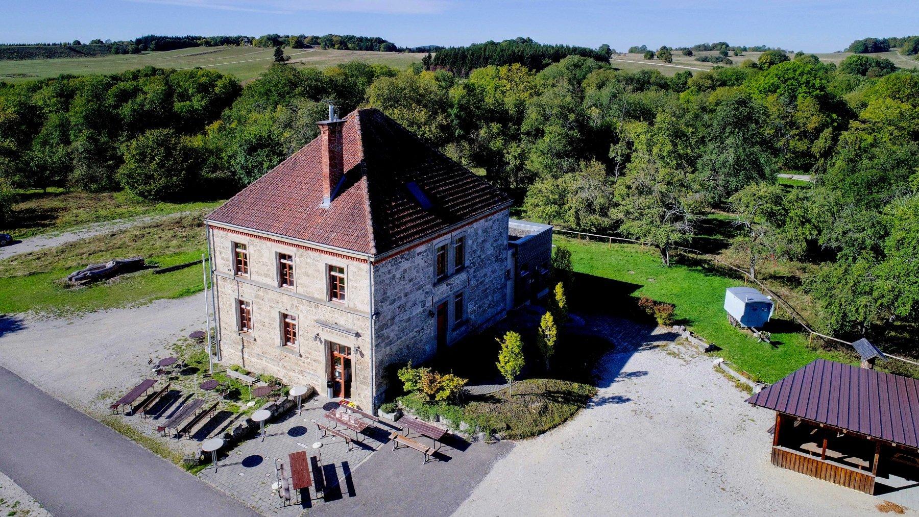 Ein historisches Haus von oben. Davor stehen einige Biertische und -bänke, drumherum sind Wiesen und Wälder. Die Sonne scheint.
