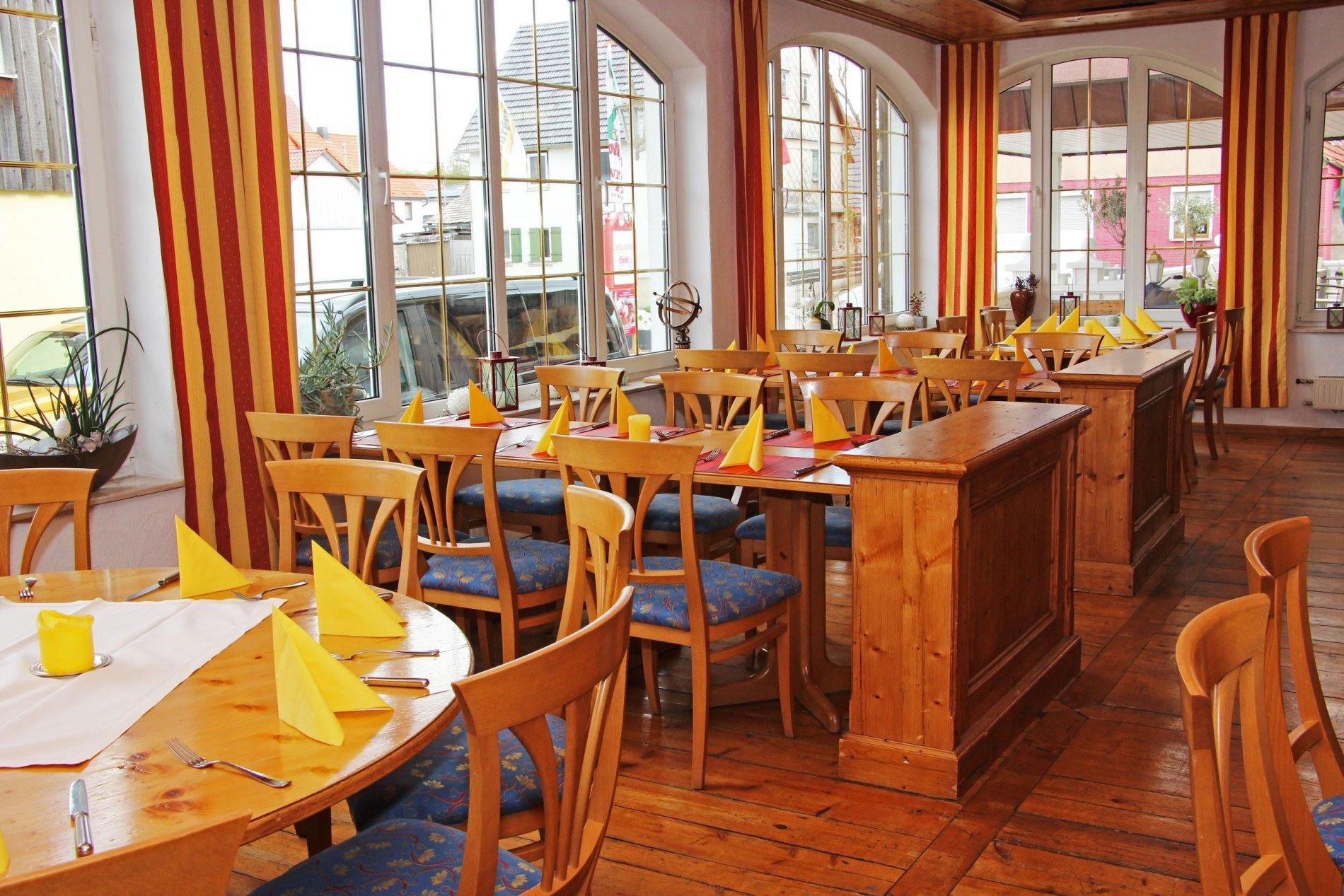 Ein heller Raum mit mehreren Fenstern, gedeckten Tischen und Stühlen.