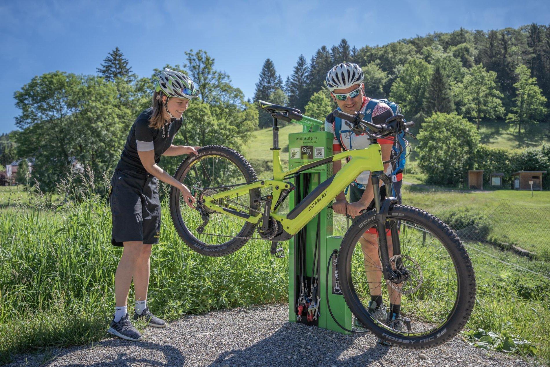 Zwei Radfahrer*innen stehen an einer Fahrradreparaturstation und hantieren an einem E-Bike, das auf dem Bikeständer hängt. Eine*r repariert die Schaltung, eine*r pumot die Reifen auf. Es ist sonnig und warm.