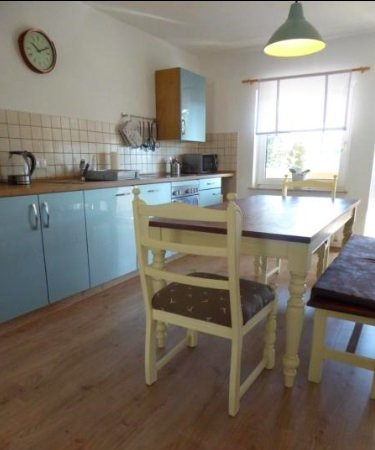 Blaue Küche mit Tisch und 3 Stühlen auf Holzboden