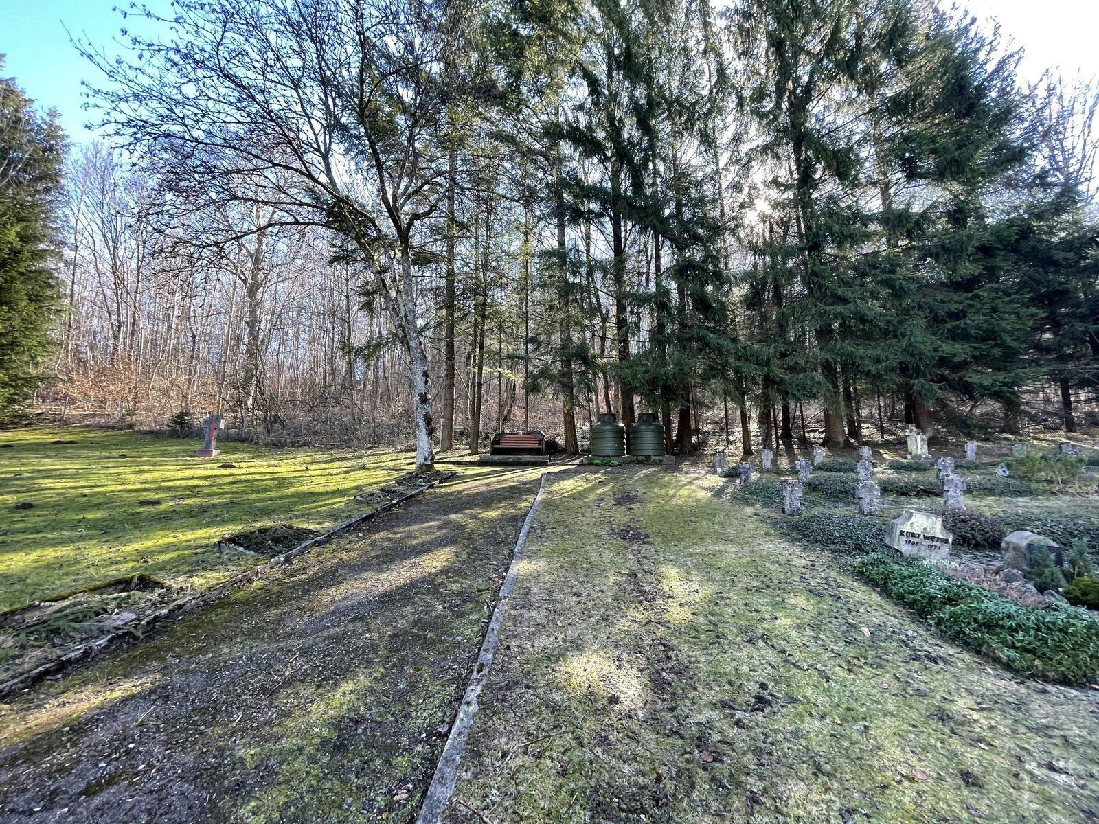 Vor einem Waldstück sind auf einer Wiese Gräber mit Grabsteinen, im Hintergrund stehen neben einer Bank zwei grüne Wasserbehälter