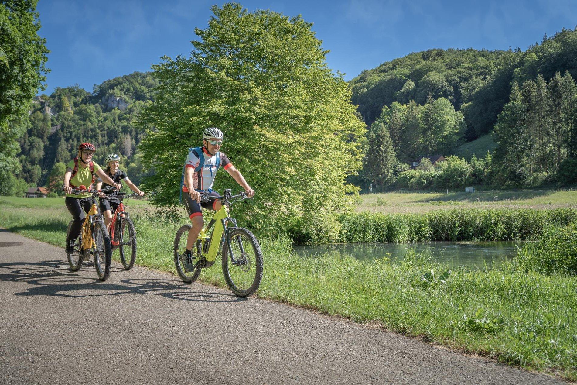 Drei Radfahrer*innen fahren mit E-Bikes auf einem Teerweg an einem Fluss entlang. Im Hintergrund ist Wald ud einige Felsen. Es ist sonnig und warm.