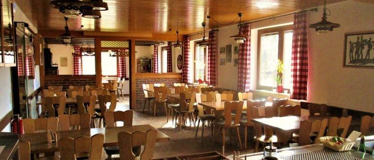 Ein Raum mit mehreren Tischen und Stühlen. Der Raum ist gemütlich mit viel Holz gestaltet.