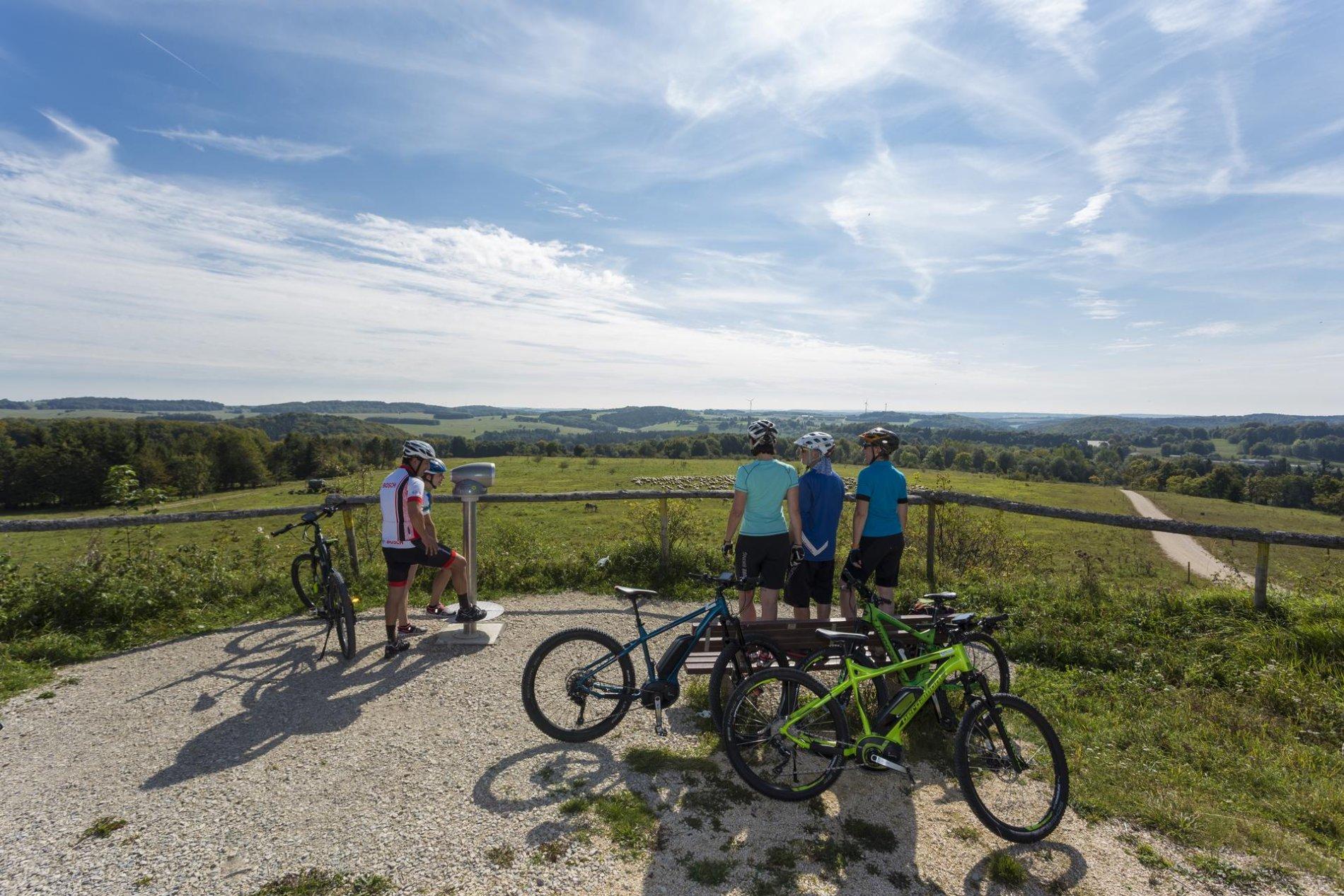Radlergruppe auf einen Aussichtspunkt mit Fernblick in die Landschaft