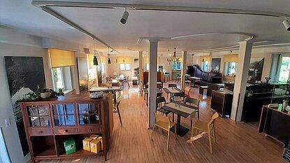 Im Gastraum stehen Tische mit bunten Stühlen. Auf den Tischen sind weiße und bunte Tischdecken.