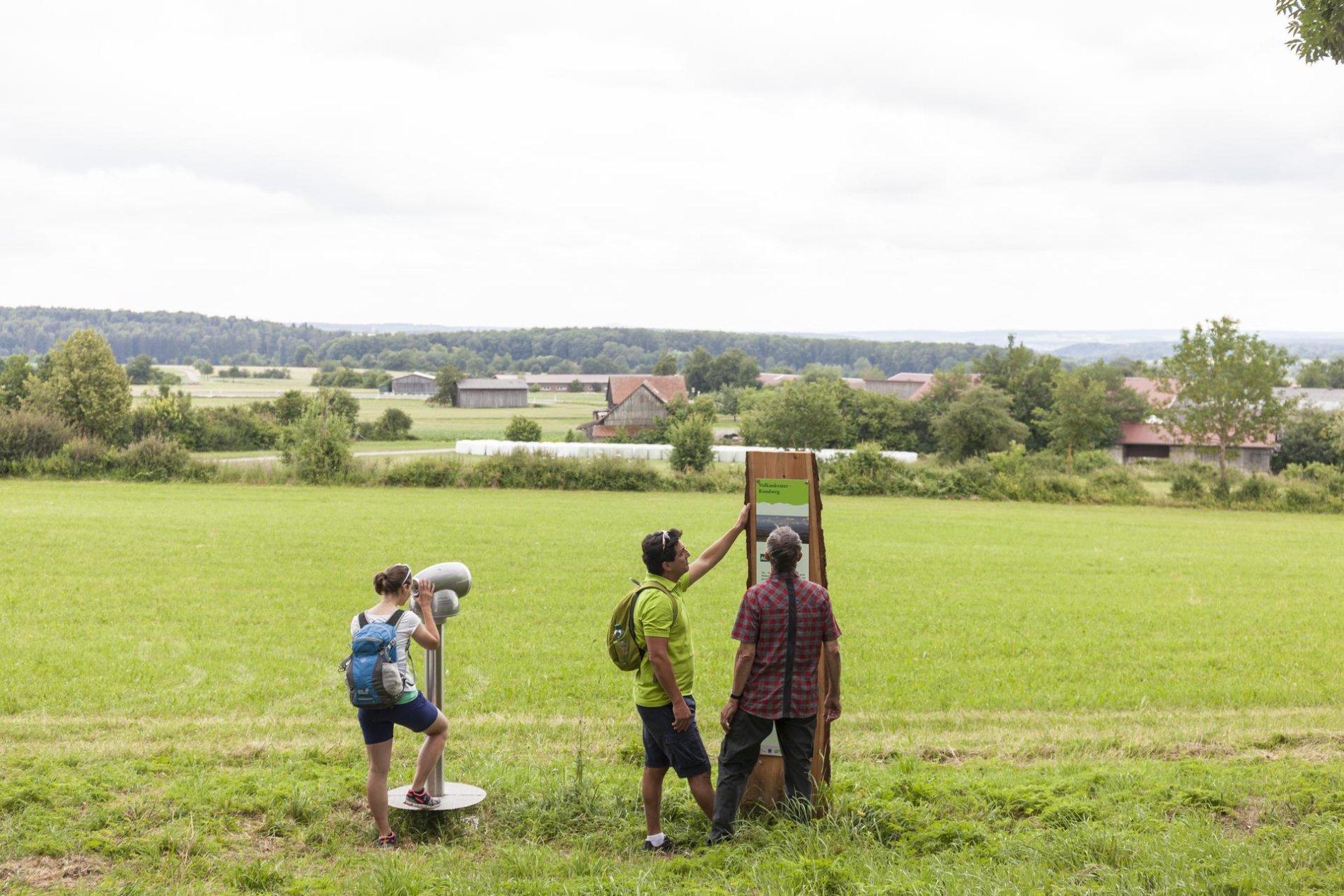 Zwei Personen stehen an einer Erklärtafel des Vulkankrater-Rundwegs und studieren die Texte. Daneben steht eine Person und blickt durch ein Viscope, das in die Richtung eines Dorfs zeigt.