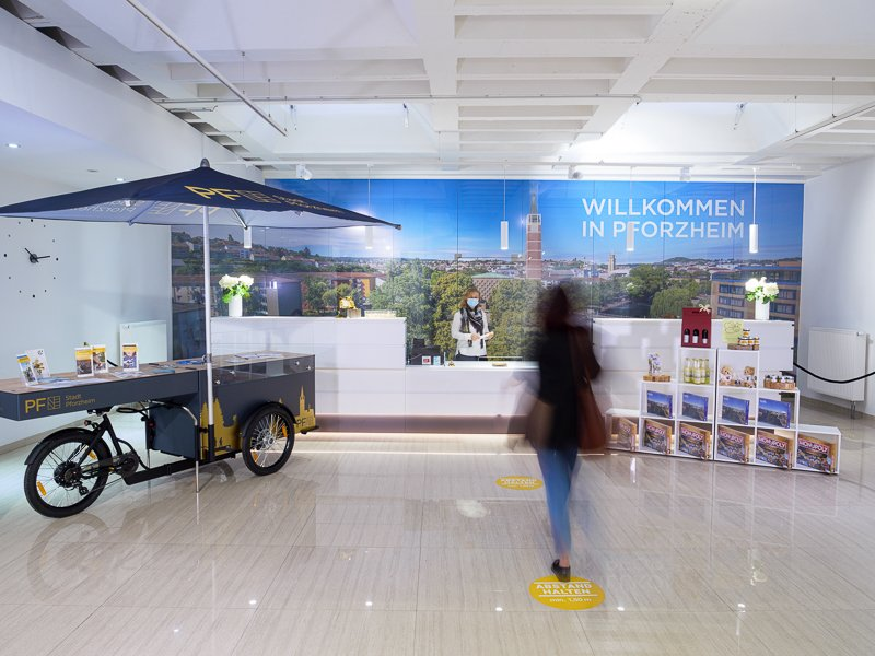 The counter with an e-bike and Pforzheim gifts. One person walks to it.