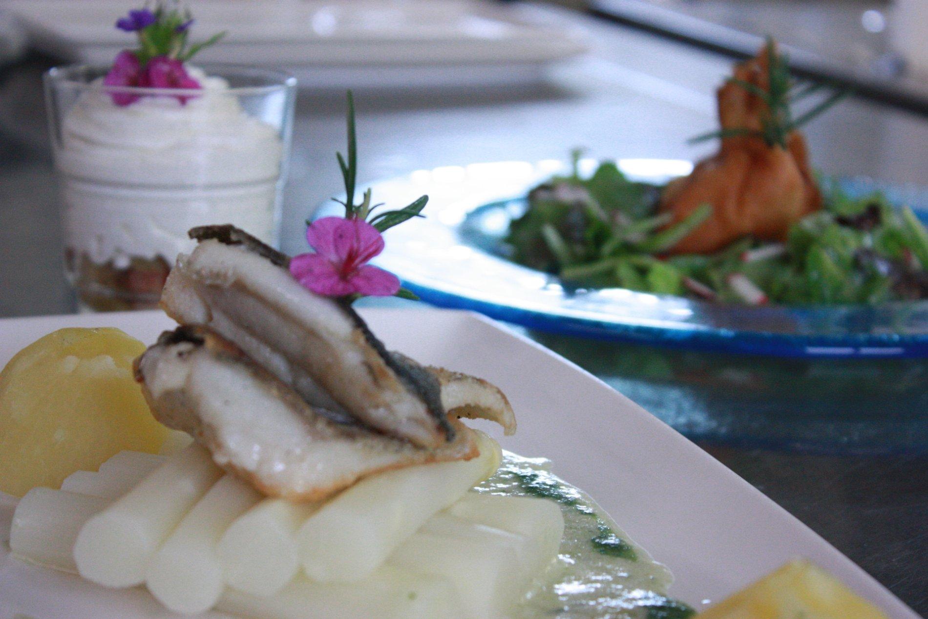 Auf einem Teller liegen schön angerichtet ein Stück Fisch, Spargel, Kartoffeln und eine helle Soße. Im HIntergrund sind verschwommen weitere Gerichte.