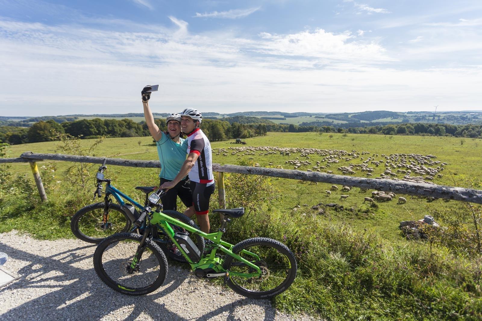Zwei Radfahrer*innen stehen mit dem Rücken zu einer Schafherde und machen mit dem Handy ein Selfie. Der Ausblick reicht über die weite Albhochfläche.