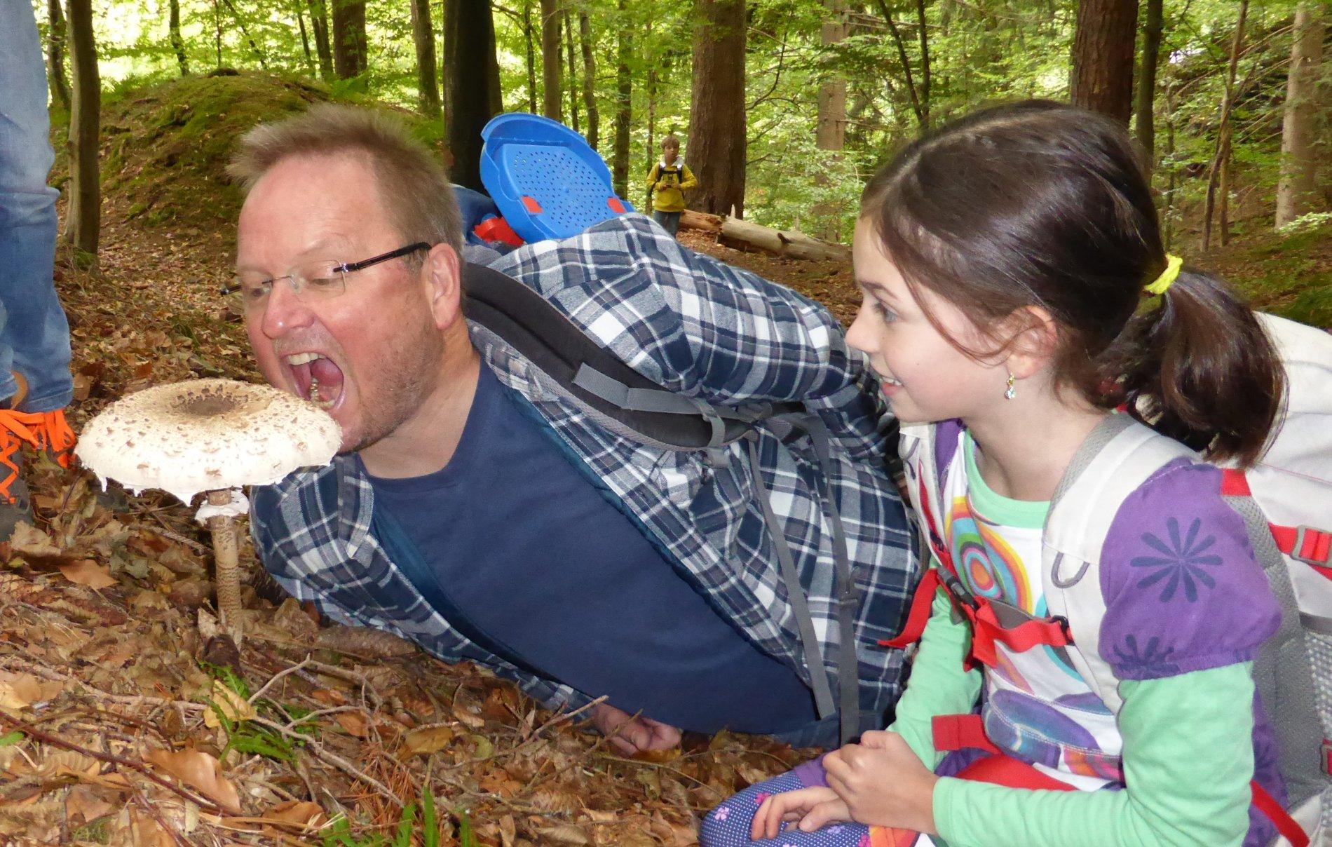 Mann und Kind im Wald vor einem Pilz