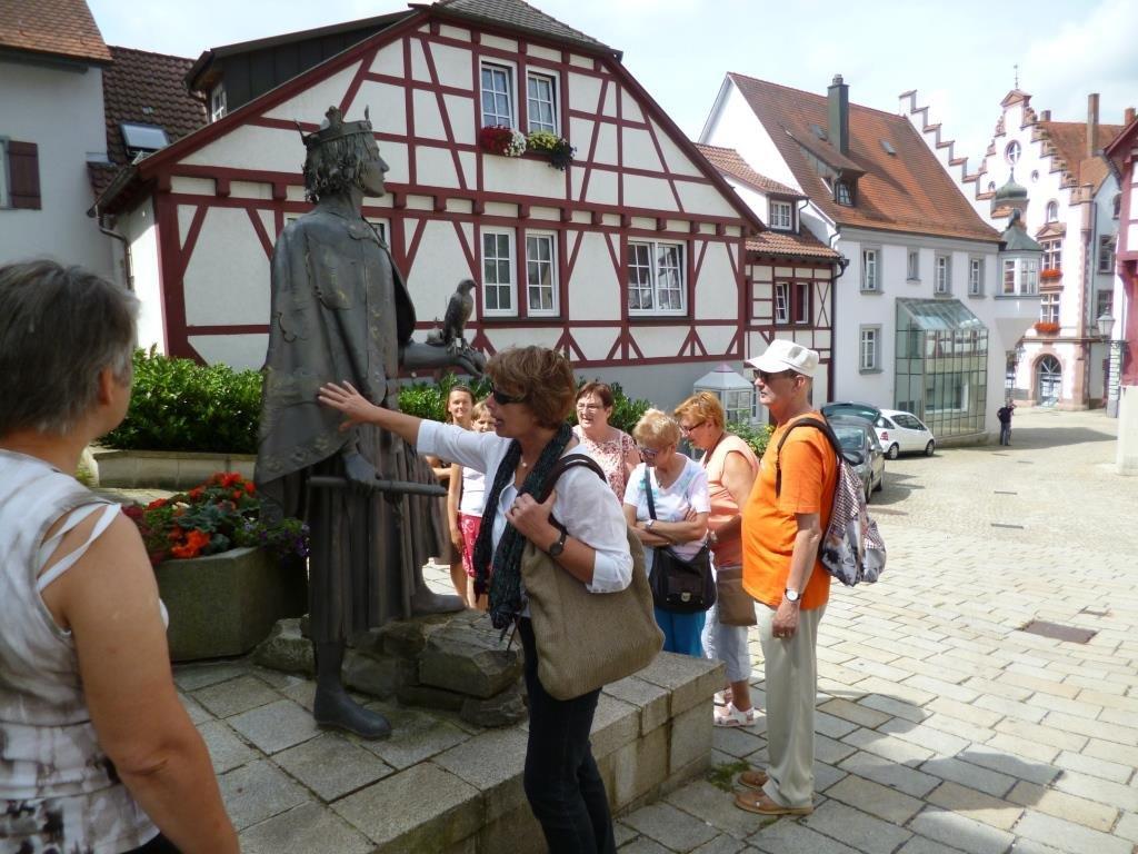 Stadtführerin zeigt auf Statue des Stauferkönig Friedrichs II.