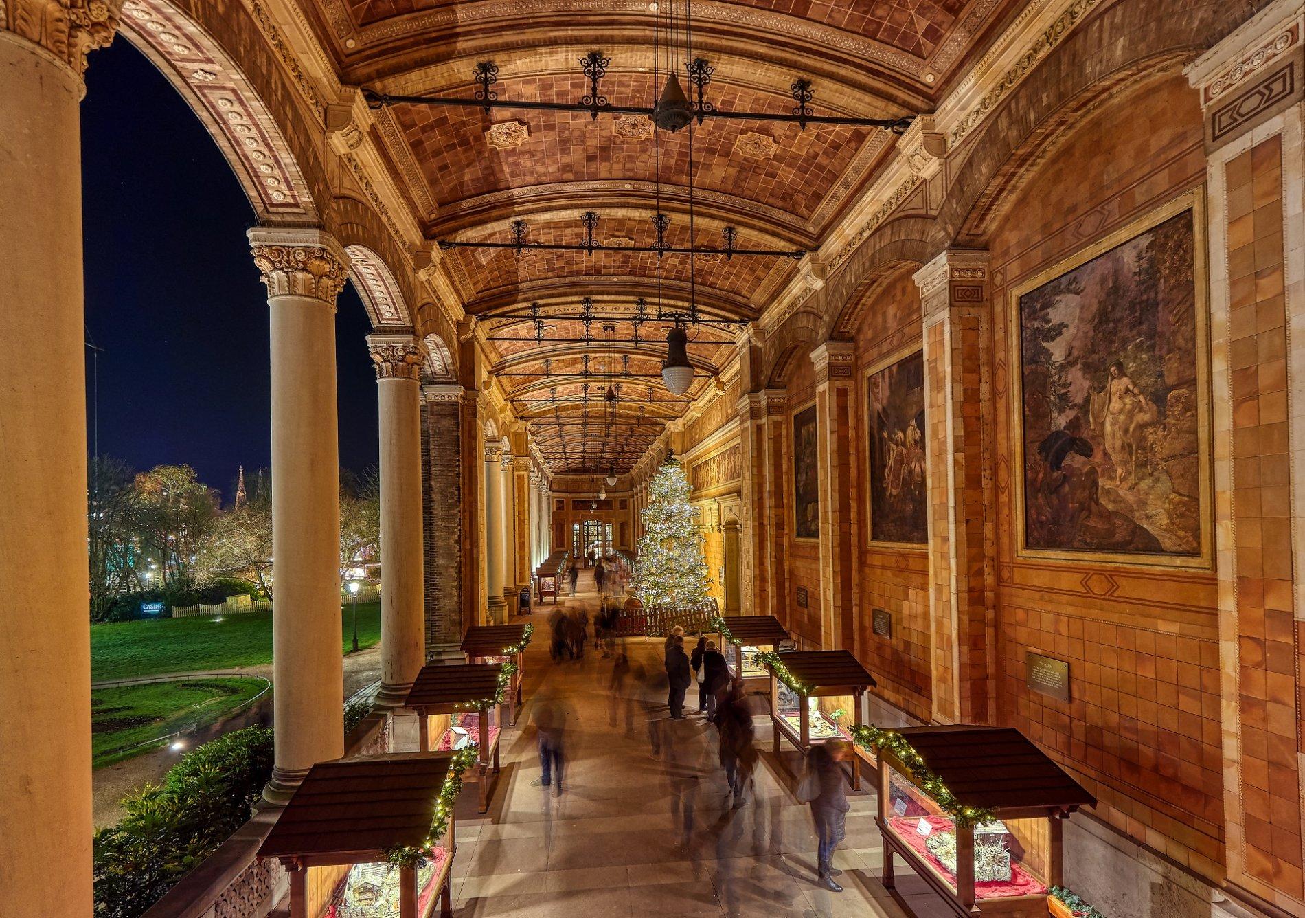 Leuchtend geschmückter Christbaum vor dem illuminierten Kurhaus Gebäude.