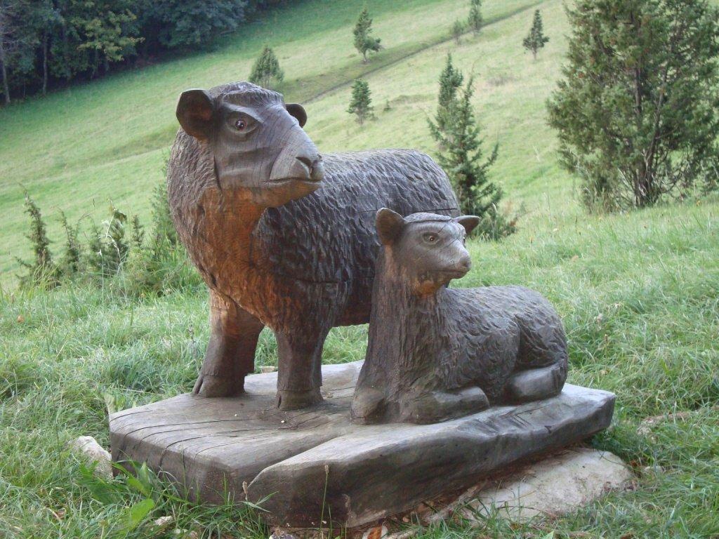 Aus Holz geschnitzte Schafe zwischen Lochen und Schafberg