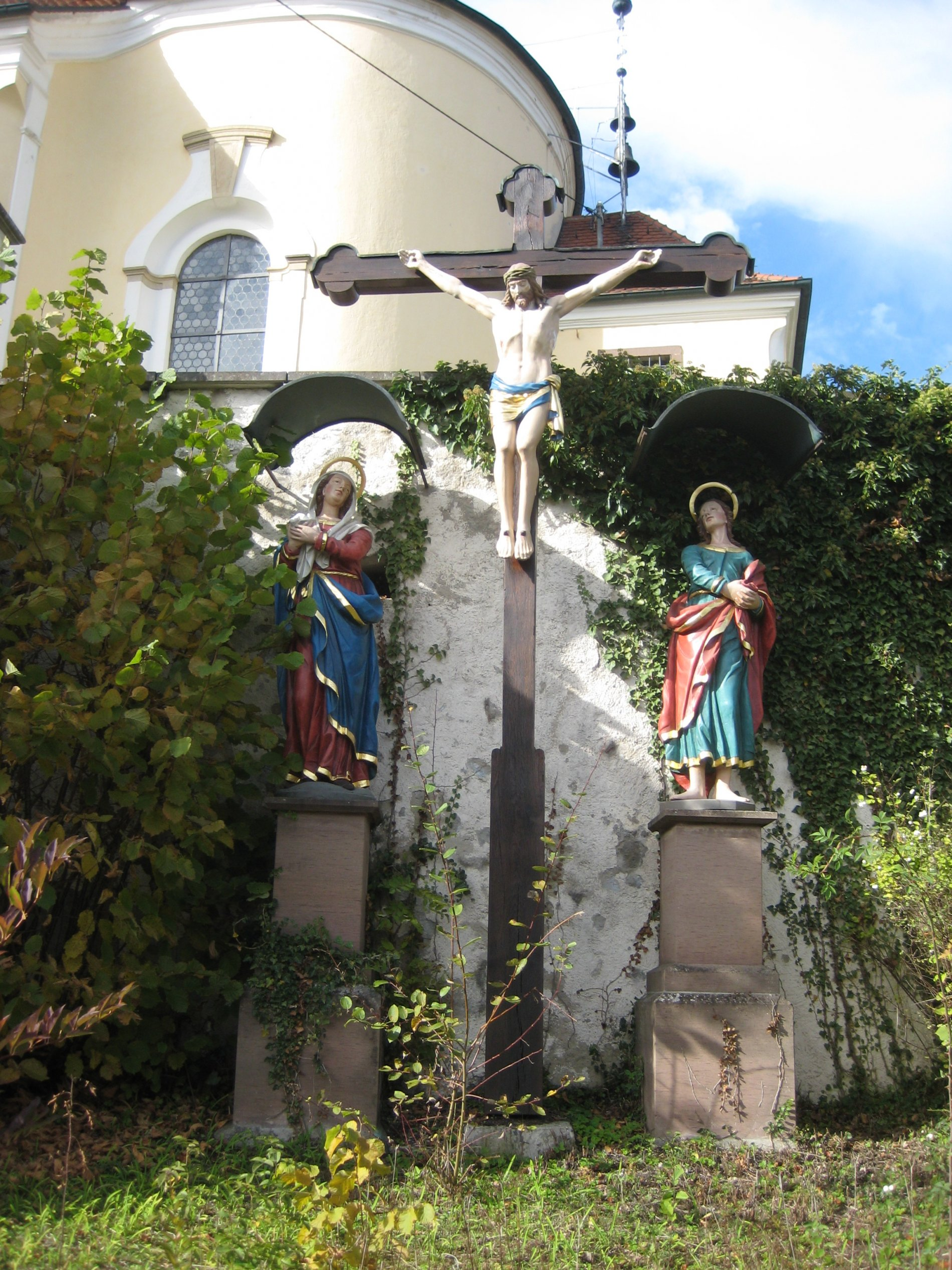 Missionskreuz mit Maria und Johannes an der Umfassungsmauer der St. Annakirche