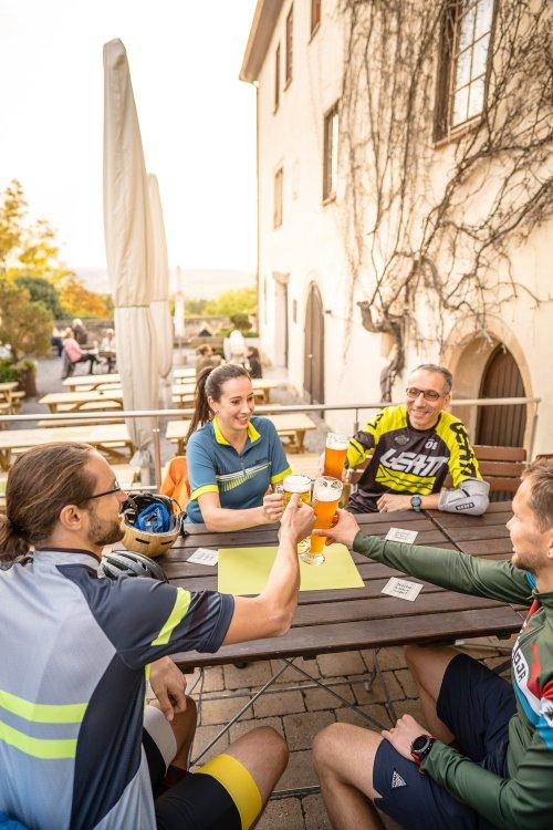 Vier Radfahrende prosten sich im Biergarten zu.