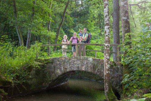 Eine Familie steht auf einer Steinbrücke über einem Bach.
